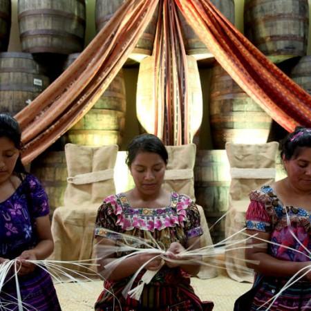 """ACOMPAÑA CRÓNICA: GUATEMALA GASTRONOMÍA. GUA08. QUETZALTENANGO (GUATEMALA), 16/02/2016.- Mujeres tejen los detalles de una botella de Ron Zacapa hoy, martes 16 de febrero de 2016, en Quetzaltenango (Guatemala). A la sombra de los volcanes, en las tierras frías del altiplano de Guatemala, se esconde un lugar, """"la casa por encima de las nubes"""", en el que se desvela cada día el secreto mejor guardado del país centroamericano: su ron. Un ron del que se venden cada año dos millones de botellas. EFE/Esteban Biba"""