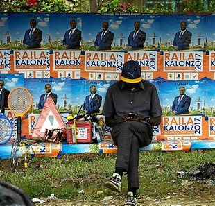 A man looks at his phone as he sits at a bus stop decorated with election campaign posters of Kenya's National Super Alliance (NASA) opposition leader and presidential candidate Raila Odinga in Nairobi on August 2, 2017. Kenya's general election will take place on August 8, 2017.  / AFP PHOTO / SIMON MAINA